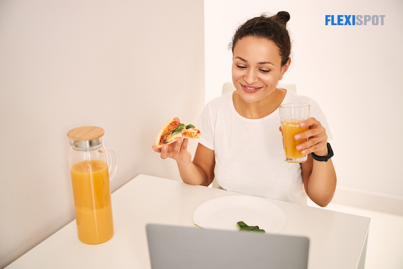 Woman eating pizza in front of laptop