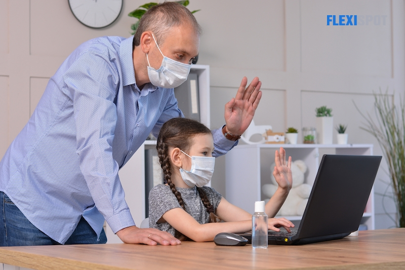 Happy father and daughter in medical masks greet with friends or teacher via laptop during coronavirus pandemic. Online communication, training, social distance, stay at home, homeschooling concept