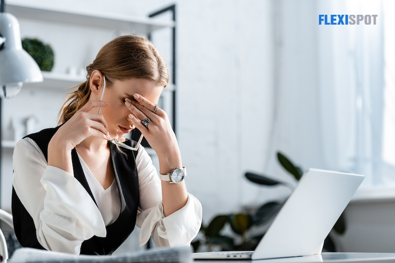 Young businesswoman doing exercises to relieve tired of computer