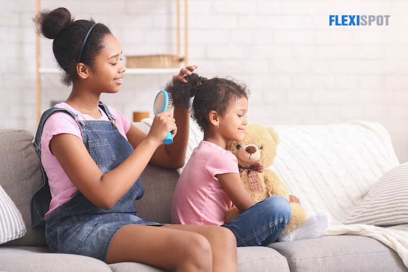 African teen girl combing younger sisters hair