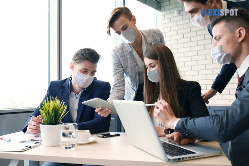 Business people wearing protective face masks while holding a presentation on a meeting during coronavirus epidemic