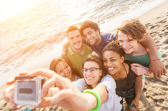 Several people are taking selfies while travelling