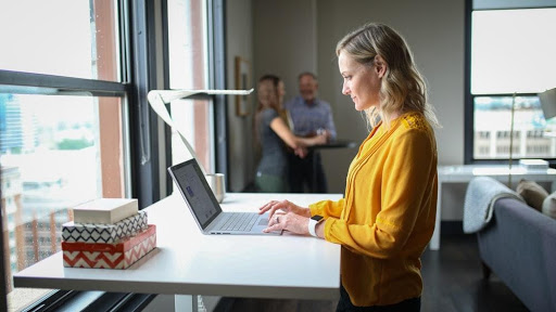 A young woman using a standing desk for work
