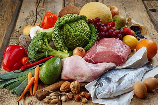 Meat, fish, nuts and vegetables spread out on a table
