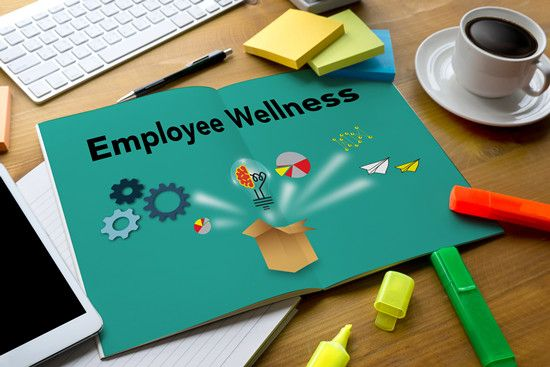 A notebook about employee wellness programs surrounded with office tools