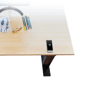 phone wirelessly charging on a standing desk