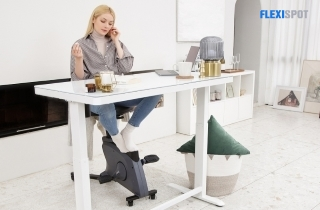 a woman working with her flexispot desk and bike