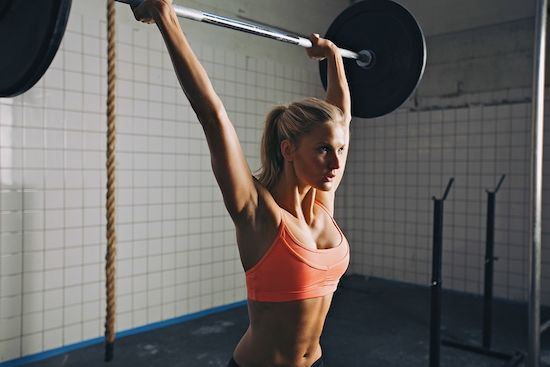 A woman performs barbell lifts
