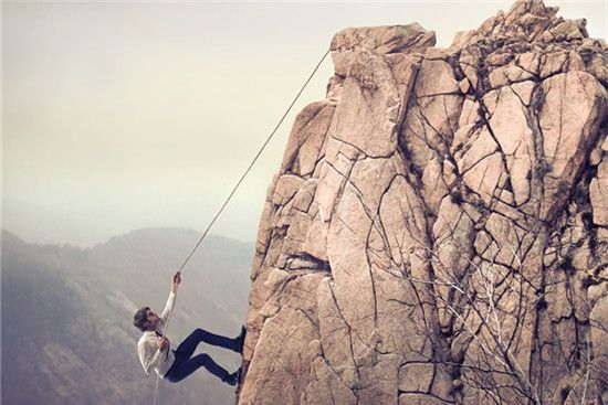 A man wearing suit is climbing a mountain