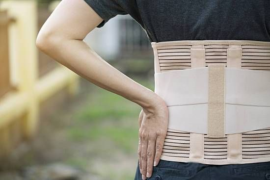 Woman wears a posture brace outside.