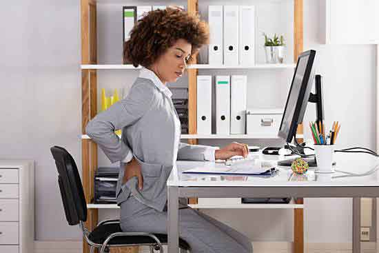 Woman soothing her back pain while she is working.