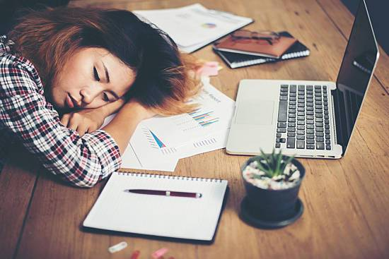 Woman falls asleep at desk in front of computer